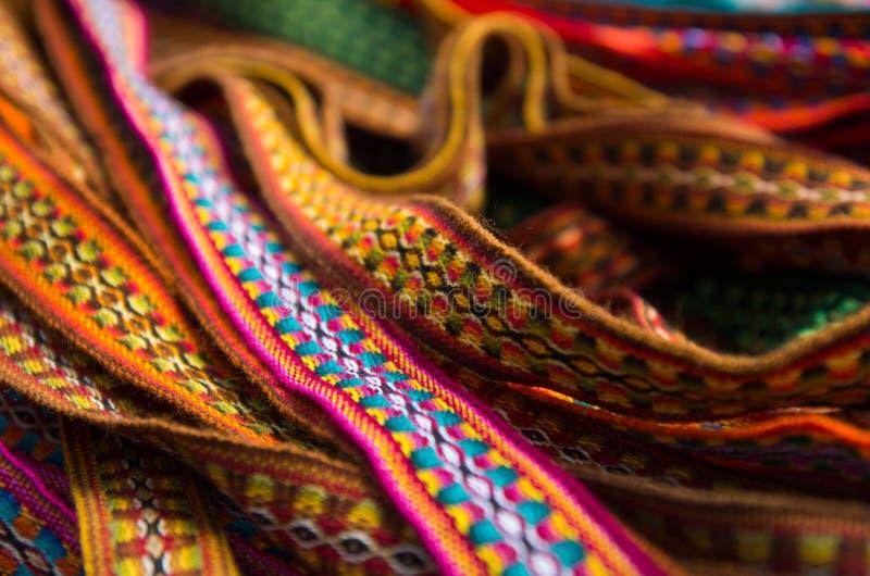 OTAVALO, EQUADOR - 17 DE MAIO DE 2017: Fio de matéria têxtil tradicional andino bonito da correia e tecido à mão nas lãs, colorid fotos de stock royalty free