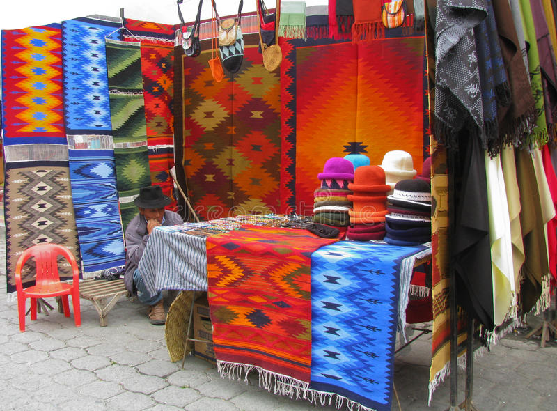 Otavalo Textile Market Stall. With stall holder crouching royalty free stock photography