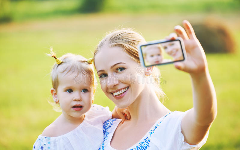 Other , baby daughter photographing selfie themselves by mobile phone in summer. Other and baby daughter photographing selfie themselves by mobile phone in royalty free stock image