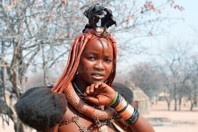 Beautiful himba young girl with national hairstyle, rings, necklace and bracelets on traditional himba village background royalty free stock photography