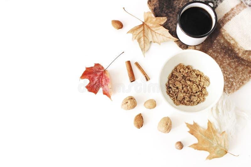 Otoño, composición del desayuno de la caída La taza del café, cuenco de avena forma escamas, muesli, manta, hojas de otoño, palil foto de archivo libre de regalías