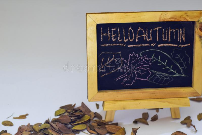 Otoño del dibujo de la mano hola en la pizarra El plano estacional del otoño pone la foto en backgroun de madera fotografía de archivo