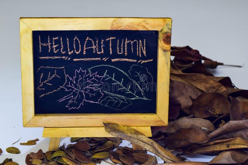 Otoño del dibujo de la mano hola en la pizarra El plano estacional del otoño pone la foto en fondo de madera fotos de archivo