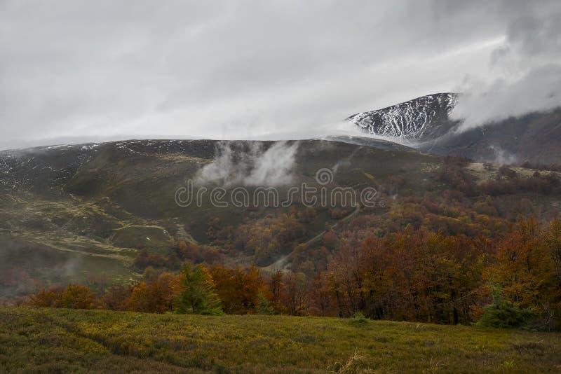 Otoño en las montañas Las montañas se cubren con la primera nieve y los árboles amarillos y rojos brillantes foto de archivo libre de regalías