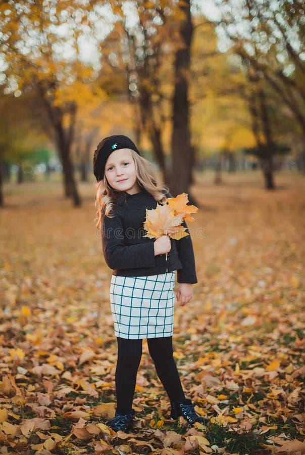 Otoño feliz Una niña en una boina roja está jugando con las hojas que caen y la risa fotos de archivo