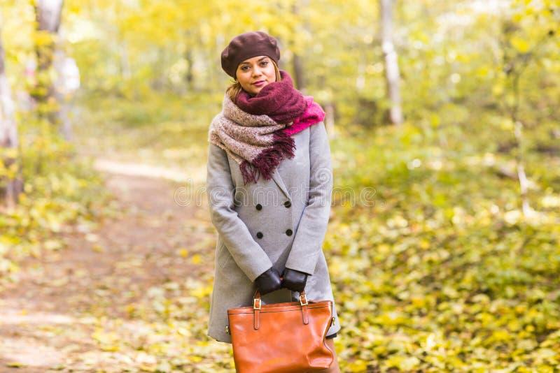 Otoño, naturaleza, concepto de la gente - mujer joven hermosa en una capa gris y una boina que se coloca en el parque imágenes de archivo libres de regalías