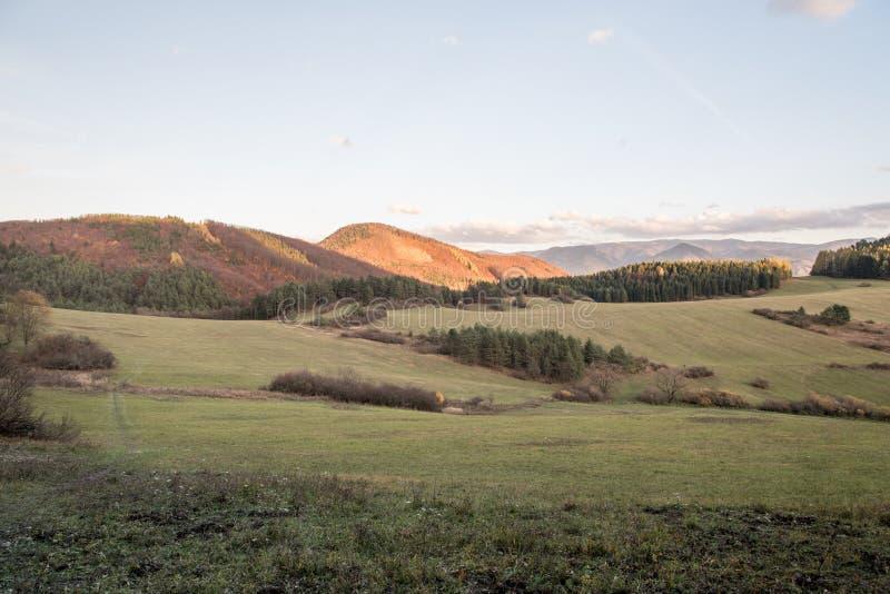 Otoño que iguala paisaje con los prados, las colinas cubiertas por el bosque colorido y el cielo azul con pocas nubes cerca del b imagenes de archivo