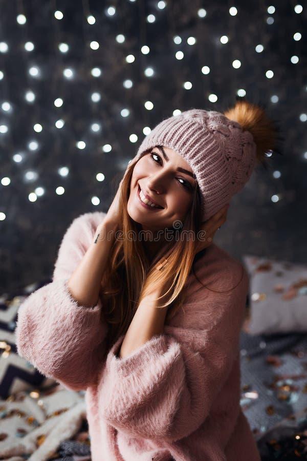 Otoño, retrato del invierno: La mujer sonriente joven se vistió en una rebeca y un sombrero de lana calientes que presentaban den foto de archivo libre de regalías