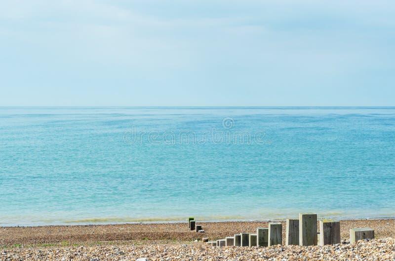 Otoczak plaża na Jaskrawym dniu z Drewnianymi poczta Prowadzi morze obrazy royalty free