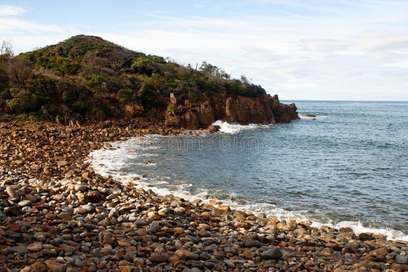 Otoczaka plażowy widok z skałami obraz stock