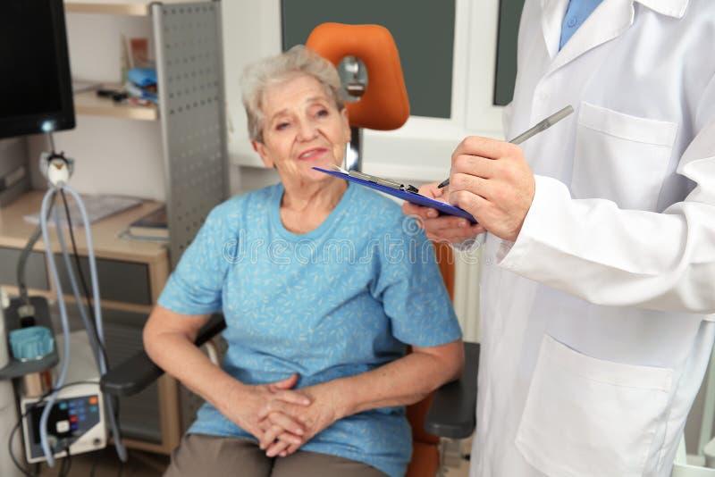 Otolaryngologist de visita da mulher superior na clínica imagem de stock royalty free