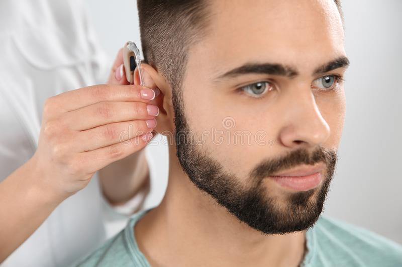 Otolaryngologist putting hearing aid in man`s ear on white. Background stock image