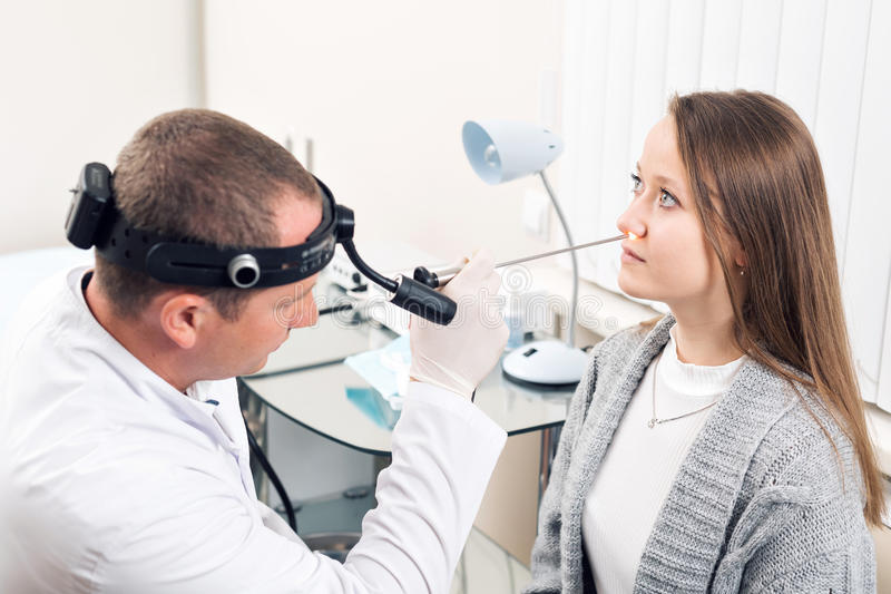 Otolaryngologist. Very attentive medical worker looking at nose of his visitor royalty free stock image