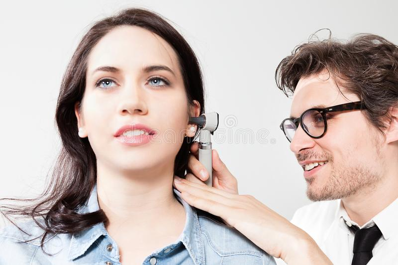 Ear Nose and Throat Examination. Otolaryngology Doctor Inspecting the ear canal and eardrum during an ENT exam royalty free stock photo