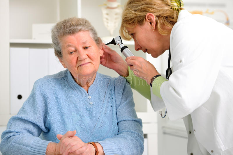 Otolaryngologycal exam. Doctor examining senior patient's ears royalty free stock photography