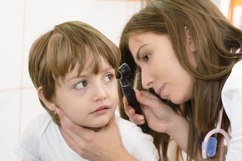 Otolaryngoloog die een jong geitjeoor onderzoeken stock foto