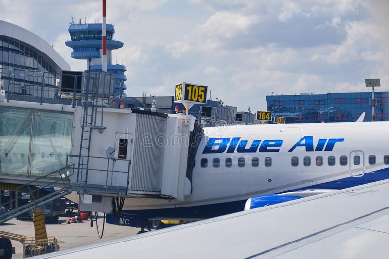 Blue Air plane connected to a passenger boarding bridge at Henri Coanda International Airport, near Bucharest, Romania stock photos