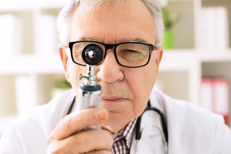 Otorrinolaringólogo que mira a través del otoscopio imagen de archivo