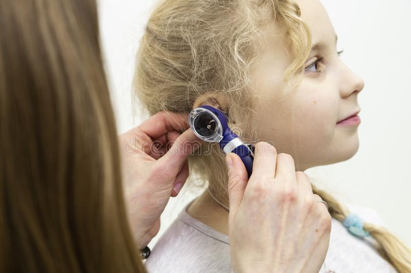 Otoscope hearing test. The doctor applies the otoscope to the ear. hearing test with a special device stock images