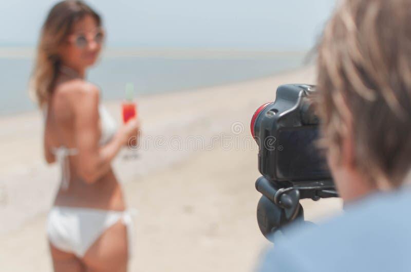 Ototshooting da jovem senhora no biquini na praia fotos de stock