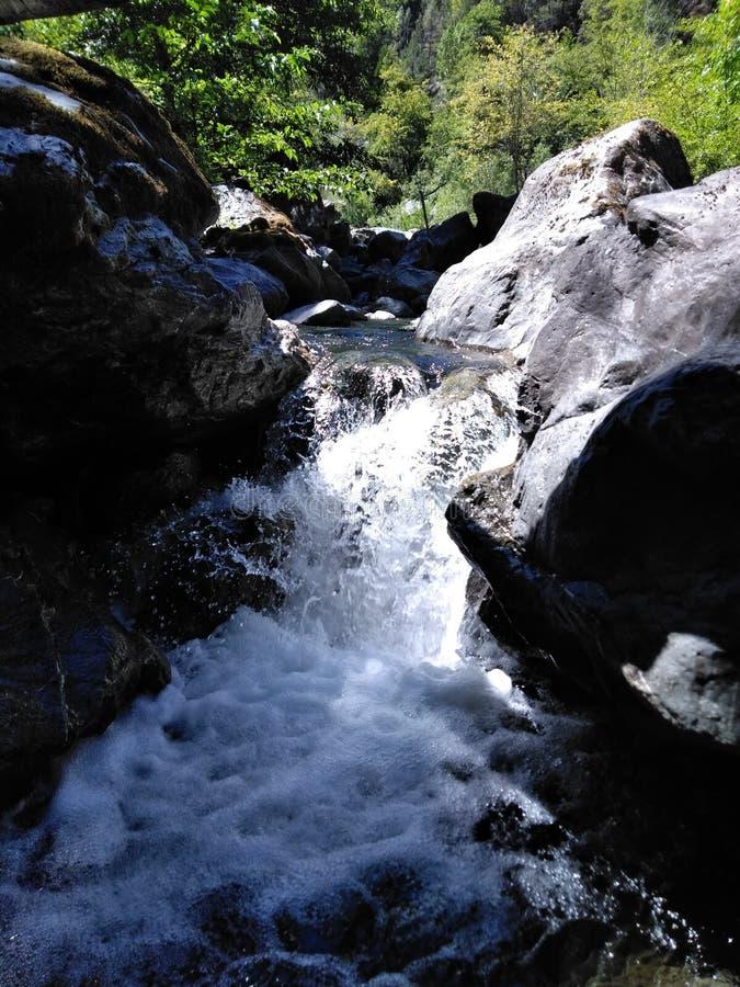 Otra vista de una cala que fluye rápida acurrucada entre las montañas foto de archivo libre de regalías