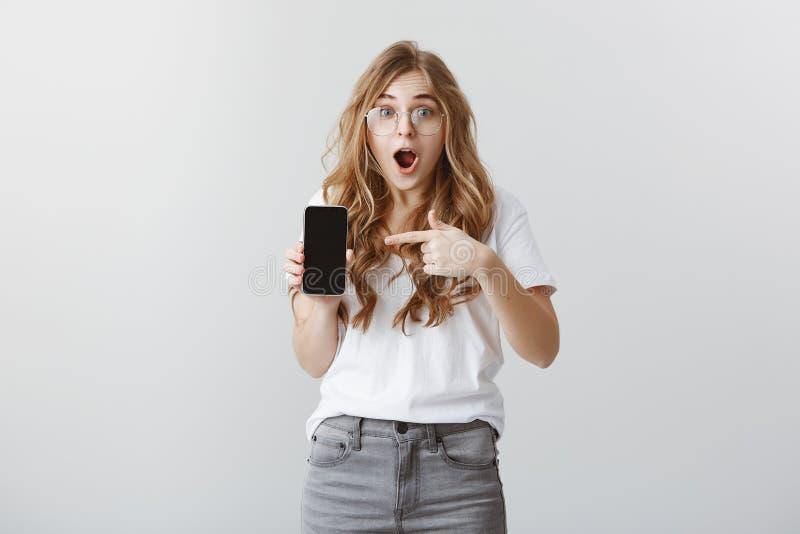 Otrolig kvalitet av smartphonen Häpen attraktiv kvinnlig modell med blont hår och exponeringsglas som visar telefonen som pekar arkivbilder