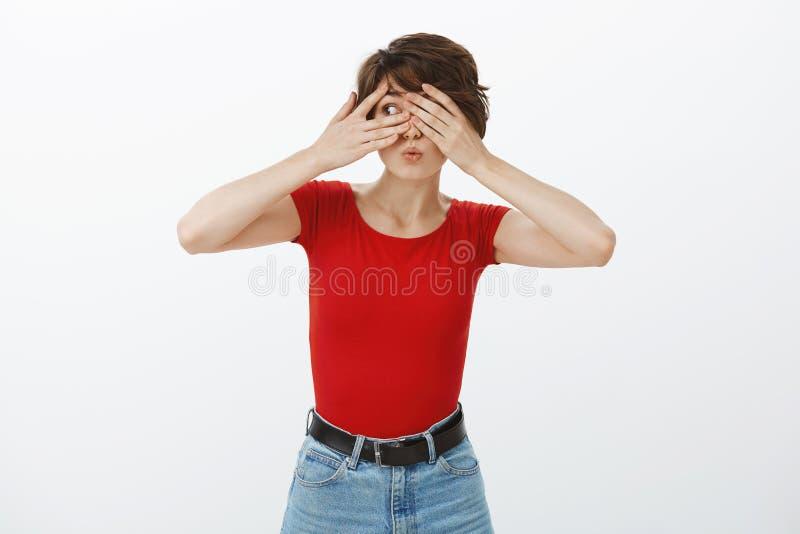 Otroligt spännande Intresserade, söta europeiska flickvän blundar med händerna som ser ut att titta genom fingrarna. royaltyfri fotografi
