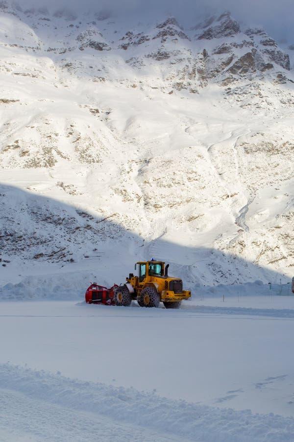 Ottan arbetar utrustning för snöborttagning i bergen arkivfoto