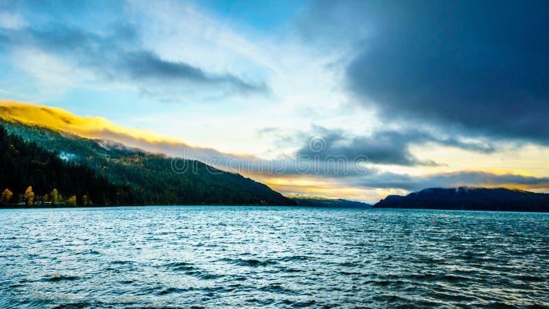 Ottasoluppgång och mörker fördunklar över Harrison Lake fotografering för bildbyråer