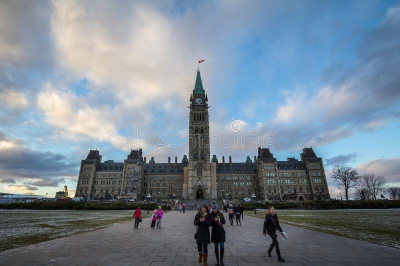 Tourists standing on front of the center bloc of the Parliament of Canada, with its Main clock tower stock images