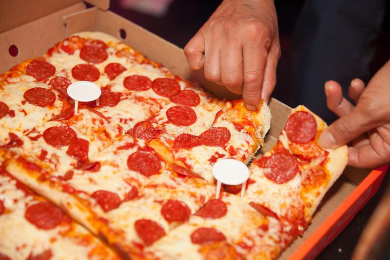 Ottenere una fetta di pizza di merguez quadrata fresca fotografia stock libera da diritti