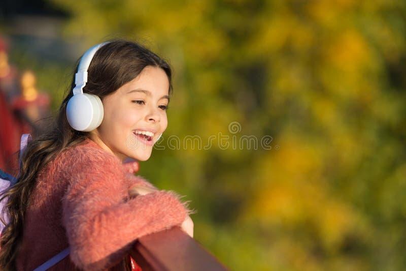 Ottenga felice Le cuffie moderne della ragazza godono di di rilassarsi Consideri il lato positivo Segreti ad allevare bambino fel immagini stock libere da diritti