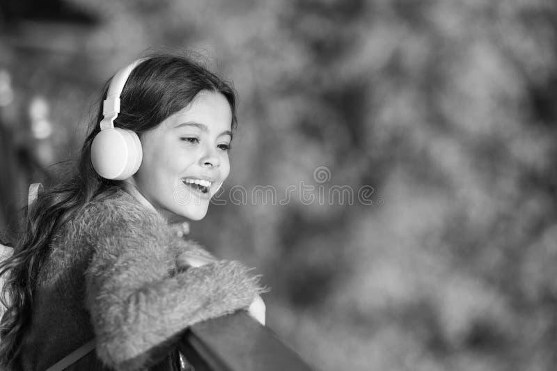 Ottenga felice Le cuffie moderne della ragazza godono di di rilassarsi Consideri il lato positivo Segreti ad allevare bambino fel fotografia stock