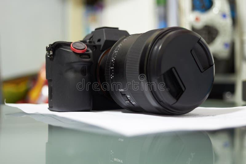 Ottica telecamera su tavolo su sfondo sfuocato fotografie stock libere da diritti