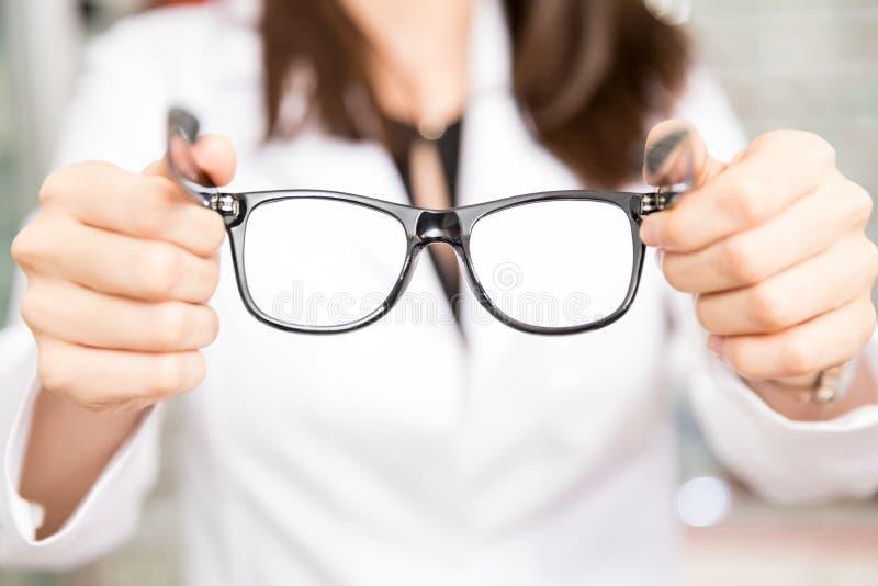 Ottico della donna che giudica gli occhiali neri della struttura disponibili fotografie stock libere da diritti