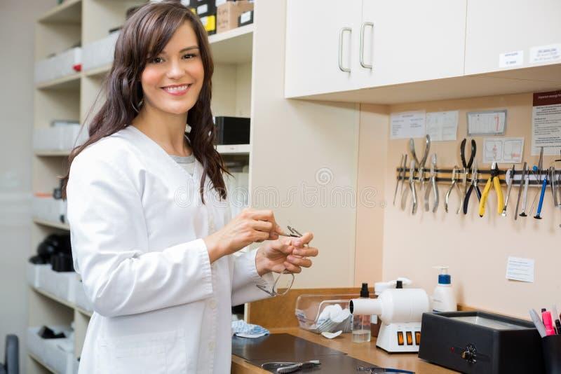 Ottico femminile felice Repairing Glasses In immagine stock