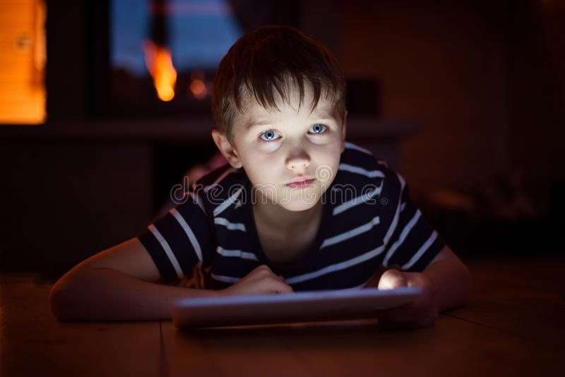 Otto anni del ragazzo che per mezzo della compressa digitale fotografie stock libere da diritti