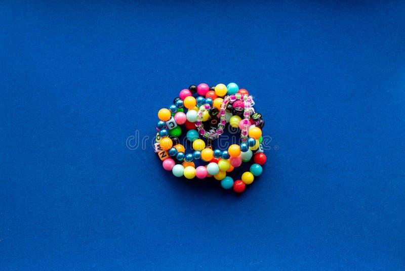 Otto braccialetti multicolori disposti in forma fiore su sfondo blu Bracelet con perline fotografia stock libera da diritti