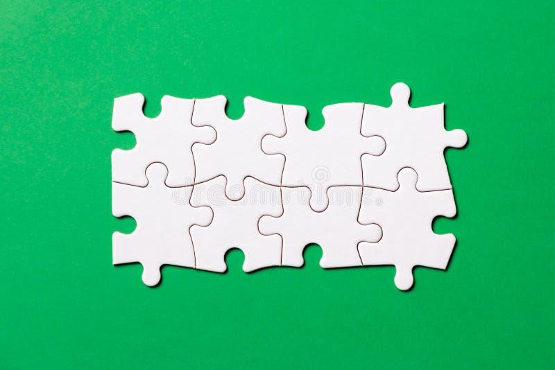 Otto pezzi del puzzle bianco su fondo verde per la presentazione di affari immagine stock libera da diritti