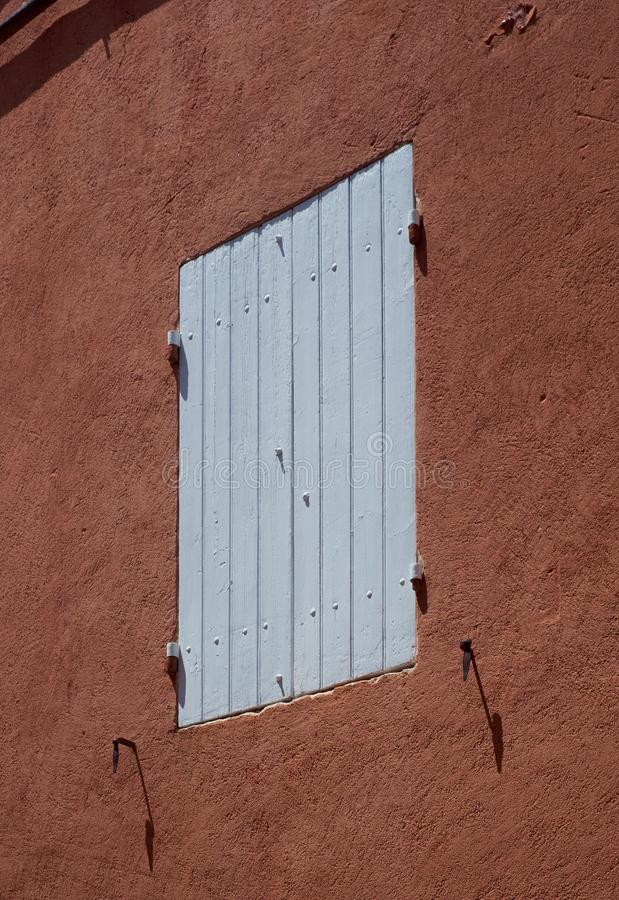 Otturatori di legno blu-chiaro di una casa ocracea rossa immagine stock libera da diritti