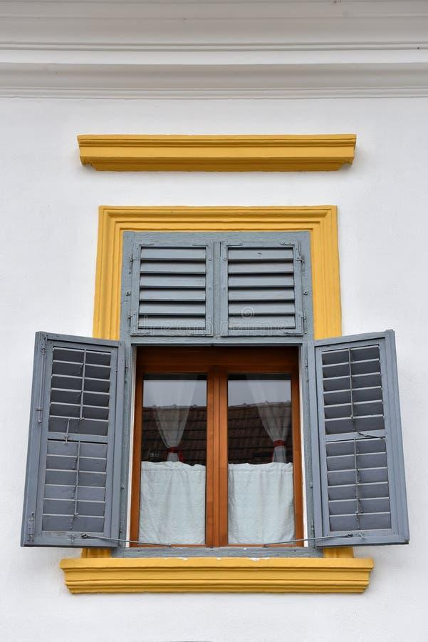Otturatori di legno gialli e grigi classici della finestra immagini stock