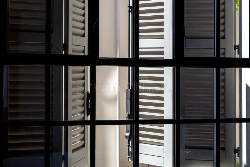 Otturatori di legno grigi su una vista di giorno soleggiato dall'interno fotografia stock