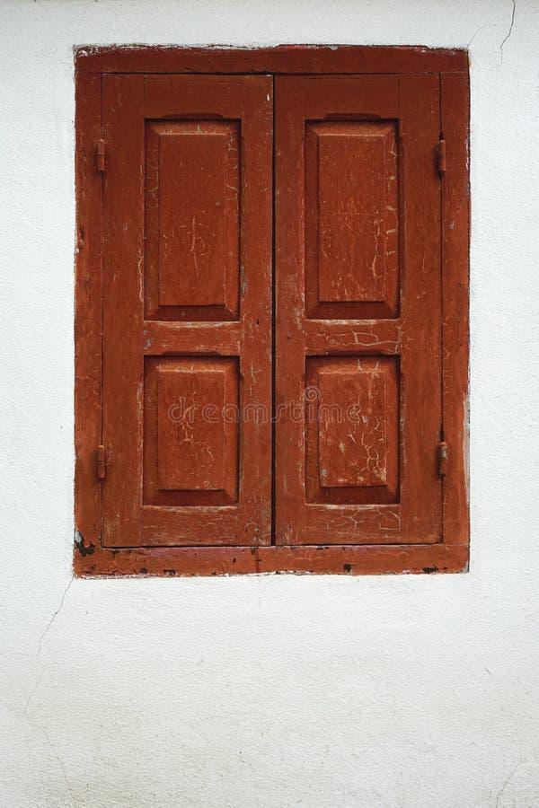 Otturatori di legno sopravvissuti della finestra con pittura fendentesi messa in una parete bianca dello stucco immagini stock libere da diritti