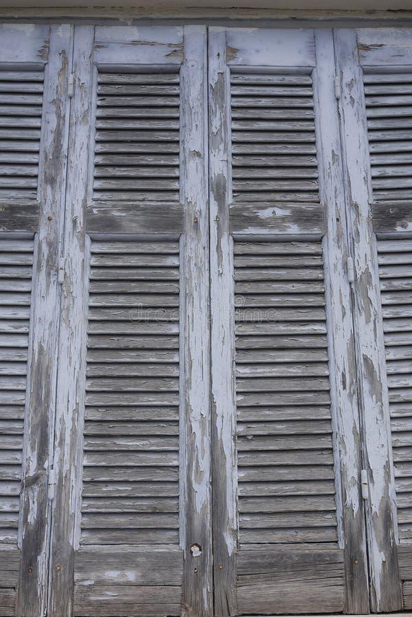 Otturatori greci della feritoia della finestra con la pittura della sbucciatura immagine stock