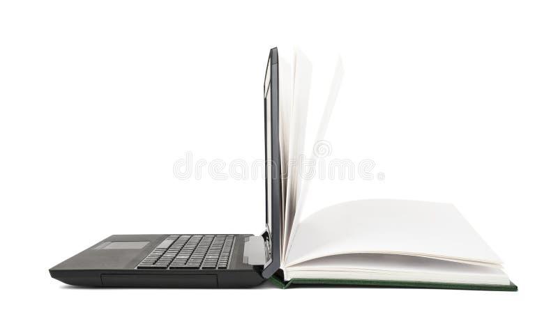 Otwarci książka zwroty w otwartego laptop zdjęcie royalty free