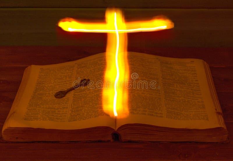 Otwarta Święta biblia jest na stole starożytny klucz Święty krzyż jarzy się nad biblią i iluminuje swój strony gorący krzyż obrazy royalty free