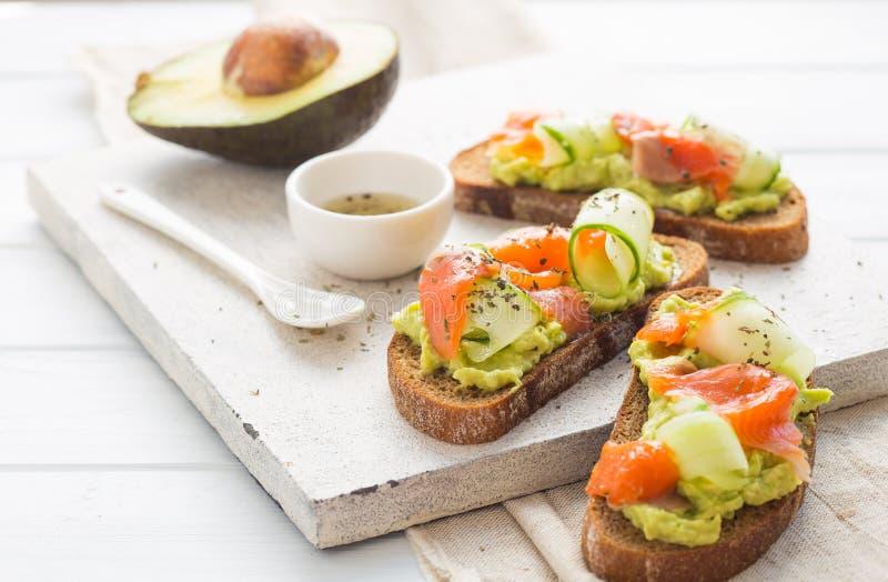 Otwarta kanapka lub grzanka Zbożowy chleb z łososiem, białym serem, avocado, ogórkiem i szpinakiem, Zdrowa przekąska, zdrowy sadł zdjęcie stock