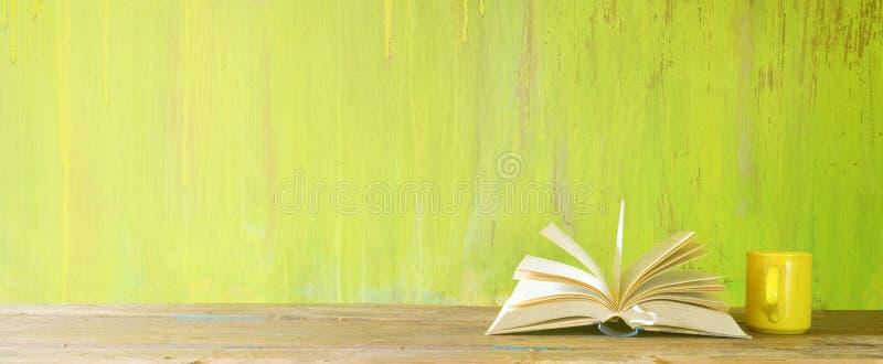 Otwarta książka i filiżanka kawy na zielonym grungy tle, czytanie, edukacja, literatura, uczenie, egzamin próbny w górę, kopii pr zdjęcia royalty free
