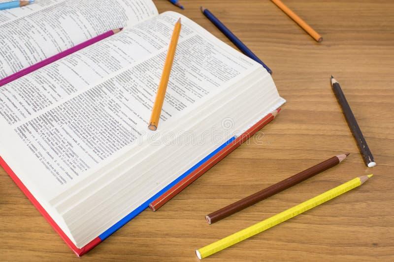 Otwarta książka i wiele barwioni ołówki na drewno stole fotografia royalty free
