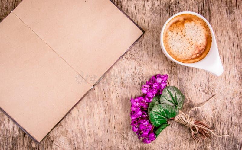 Otwarta książka z pustymi stronami, wiosna kwiatami i filiżanką kawy, Kawa i fiołki na drewnianym tle Romantyczny pojęcie fotografia royalty free